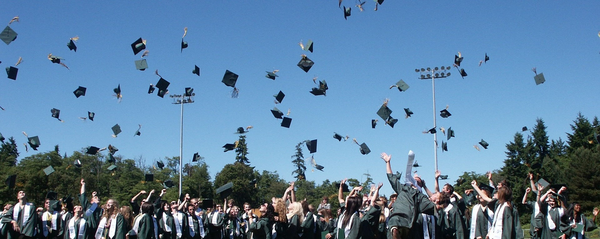 students throwing mortarboards at graduation